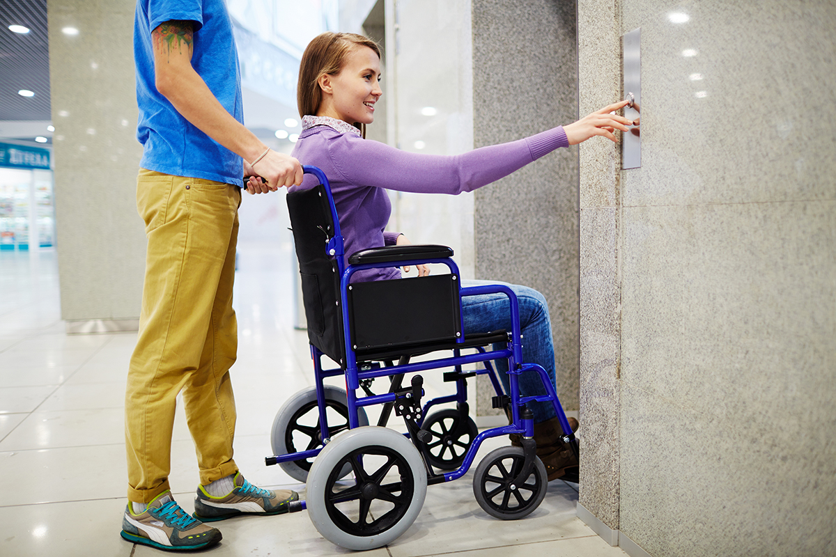 Assistant and handicapped young woman in wheelchair waiting for elevator, she pressing button by herself and smiling