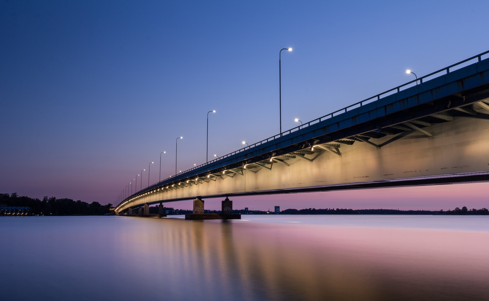 gray concrete bridge with body of water during nighttime